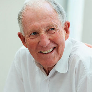 80 year old man smiling in a white shirt.